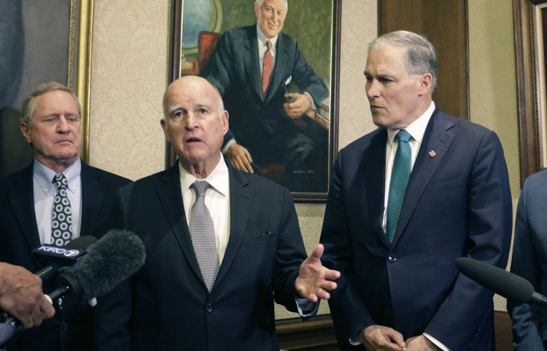 Former California Gov. Jerry Brown, third from left, speaks to the media as Washington Gov. Jay Inslee, second from right, looks on, in Olympia, Wash., Thursday, Jan. 17, 2019. Inslee, Brown and several Washington lawmakers met to discuss Inslee's climate agenda. (AP Photo/Rachel La Corte) RPRL103 RPRL103