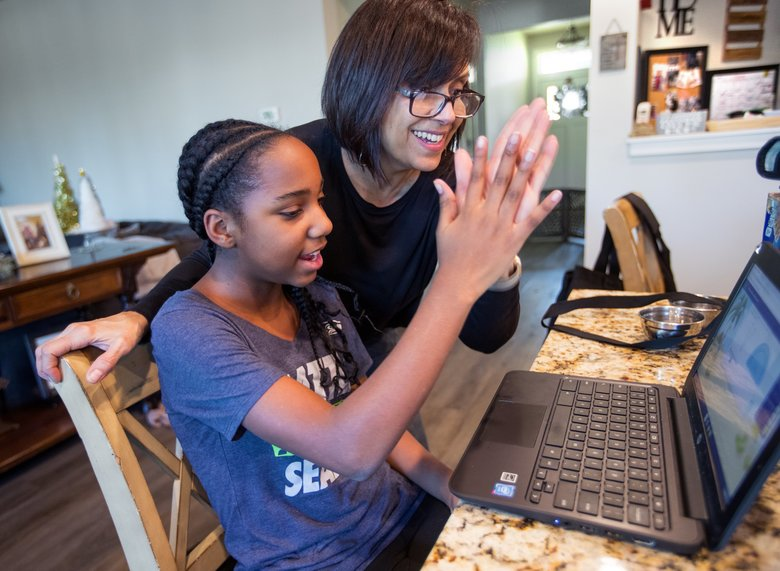 Isabella Warner, left, gets a high-five from her mom, Ana, when the math problem they worked on turned out correctly. (Mike Siegel / The Seattle Times)