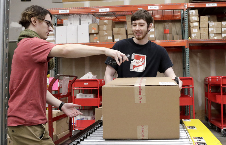 FILE – In this Nov. 16, 2018, file photo, Target employees sort boxed items from online orders to be shipped out to customers at at a Target store in Edison, N.J. For many retailers that have lifted pay to attract and keep workers, another challenge has arisen: Making those workers productive enough to justify the larger payouts. (AP Photo/Julio Cortez, File)