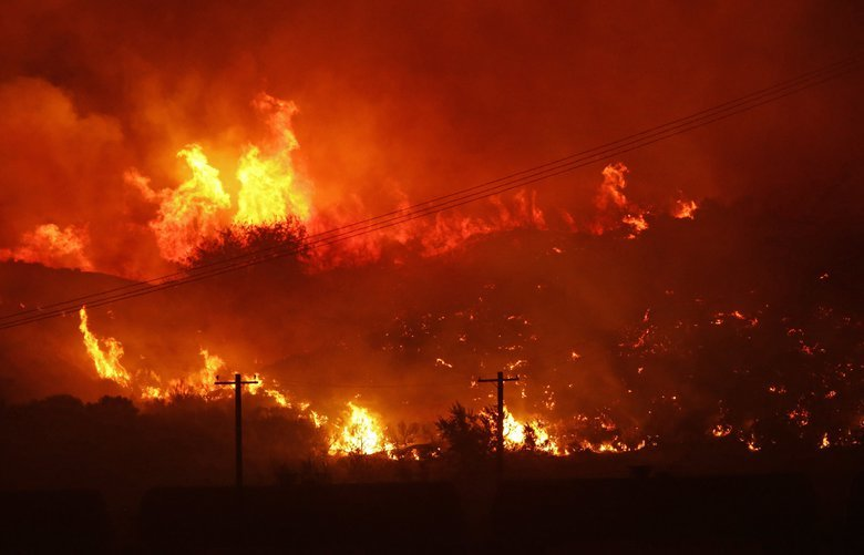 A wildfire burns next to power lines near Othello, Wash., early Sunday, Aug. 13, 2017. (AP Photo/Ted S. Warren) WATW101