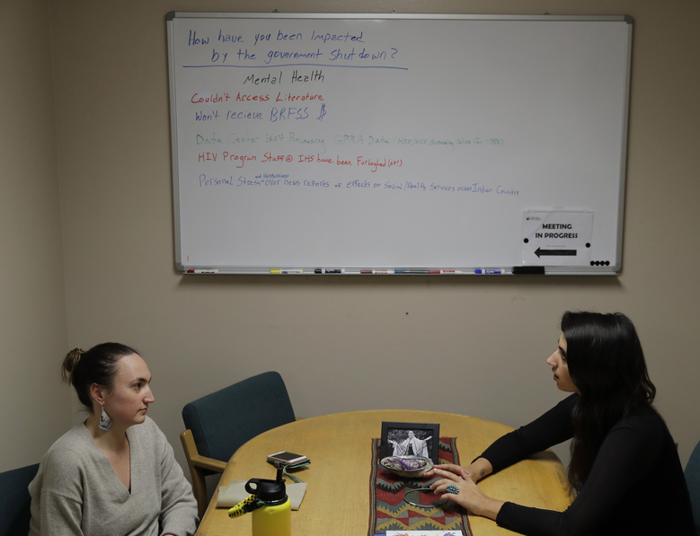 Caitlin Marie-Lieb Keller, left, and Sofia Locklear, right, both employees of the Urban Indian Health Institute in Seattle, have a meeting in front of a white board used for an earlier discussion of the federal government shutdown, Friday, Jan. 11, 2019, in Seattle.   Fallout from the federal government shutdown is hurting hundreds of Native American tribes and entities that serve them. The pain is especially deep in tribal communities with high rates of poverty and unemployment, and where one person often supports an extended family.  (AP Photo/Ted S. Warren)