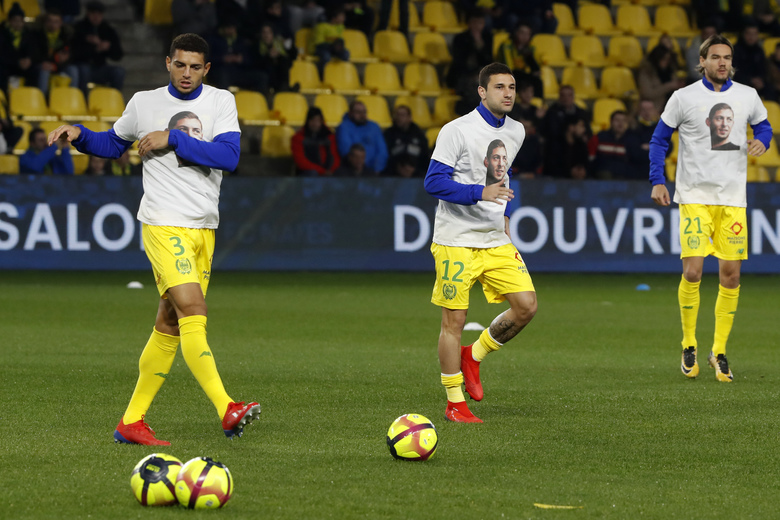 Nantes players Diego Carlos, left, Nantes' Gabriel Boschilia, center, and Rene Krhin wear jerseys showing Argentinian player Emiliano Sala in La Beaujoire stadium as they train before the French soccer League One match Nantes against Saint-Etienne, in Nantes, western France, Wednesday, Jan.30, 2019. Sala disappeared over the English Channel on Jan. 21, 2019 as it flew from France to Wales. Sala had just been signed by Premier League club Cardiff. (AP Photo/Thibault Camus)
