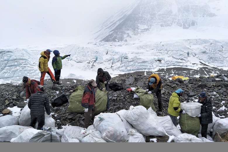 FILE – In this May 8, 2017, file photo released by Xinhua News Agency, people collect garbage at the north slope of the Mount Qomolangma in southwest China's Tibet Autonomous Region. China announced Monday, Jan. 21, 2019 that it plans to cut the number of climbers attempting to scale Mount Everest from the north by 1/3 this year as part of plans for a major cleanup on the world's highest peak. (Awang Zhaxi/Xinhua via AP)