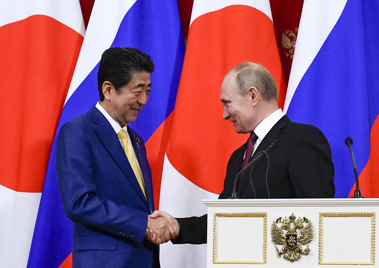 Russian President Vladimir Putin, right, shakes hands with Japanese Prime Minister Shinzo Abe, after their joint news conference following the talks in the Kremlin in Moscow, Russia, Tuesday, Jan. 22, 2019.  The Kremlin talks focused on a decades-long territorial dispute between the two nations. (Alexander Nemenov/Pool Photo via AP)
