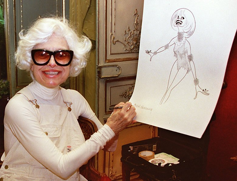 FILE – In this Nov. 1, 1997 file photo, actress Carol Channing hand-signs a lithograph of herself by caricaturist Al Hirschfeld at her home in Beverly Hills, Calif.  Channing, whose career spanned decades on Broadway and on television has died at age 97. Publicist B. Harlan Boll says Channing died of natural causes early Tuesday, Jan. 15, 2019 in Rancho Mirage, Calif. (AP Photo/Damian Dovarganes, File)