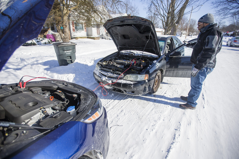 Jason Johnson helps his son Jacquio jump start his car Wednesday, Jan. 30, 2019 on the south side of South Bend, Indiana. (Michael Caterina/South Bend Tribune via AP)