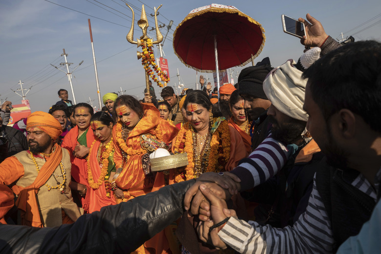 "In this Jan. 15, 2019, photo, Laxmi Narayan Tripathi, center left, a transgender activist and founder of the ""Kinnar Akhara"" monastic order arrive with other members of the order for a spiritual-cleansing dip on the auspicious Makar Sankranti day during the Kumbh Mela festival in Prayagraj, Uttar Pradesh state, India. Kinnars celebrated their inclusion at Kumbh as a victory, but their greater acceptance by Hinduism's most powerful leaders, in the religious and political spheres, remains to be seen. Unlike other akharas, which are only open to Hindu men, Kinnar, founded in 2015, is open to all genders and religions. (AP Photo/Bernat Armangue)"