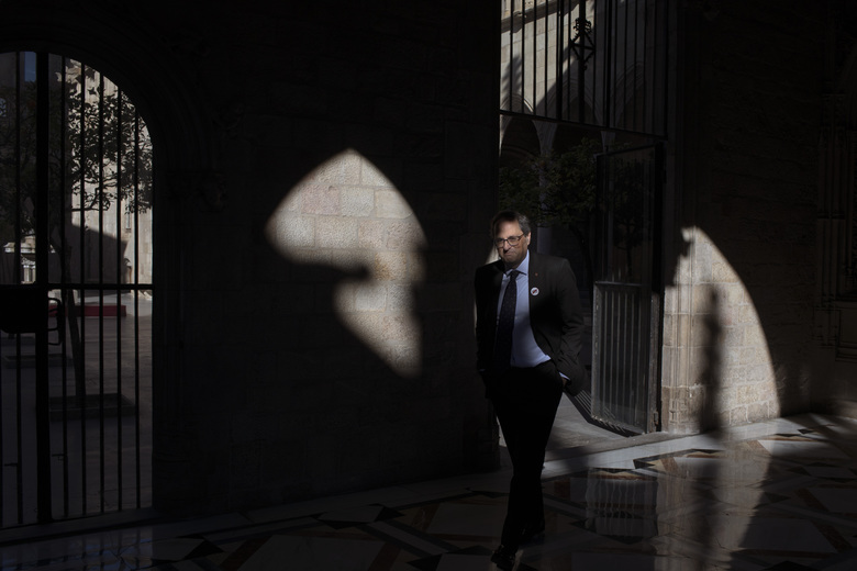 In this Thursday, Jan. 10, 2019 photo, Catalan regional president Quim Torra walks at the Palace of Generalitat or Catalan government headquarters, ahead of an interview with The Associated Press, in Barcelona, Spain. Catalonia separatist leader says that the Spanish government's bid to pass a national budget is doomed unless the wealthy northeastern region is allowed to hold a referendum on secession from the rest of the country. (AP Photo/Emilio Morenatti)