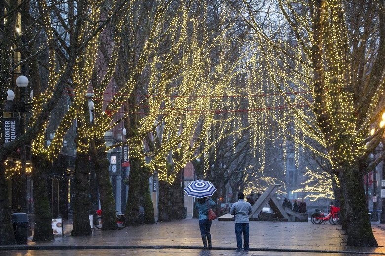 People pause to take photos of snow and the string lights Sunday in Occidental Park in Seattle's Pioneer Square neighborhood. (Bettina Hansen / The Seattle Times)