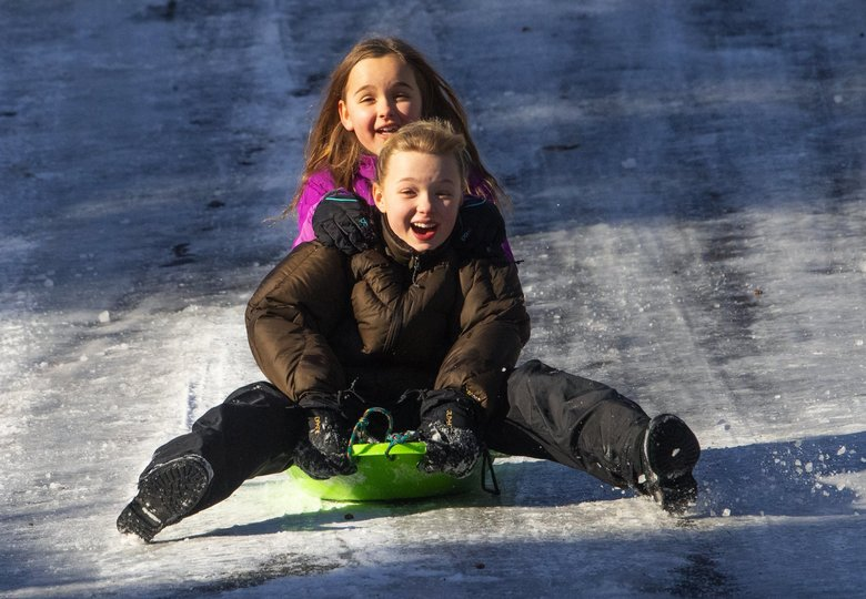 Calla Walker, 10, (foreground) and Lillian Kohrmann, 9, both students at Three Tree Montessori in Burien and off school for the second day in a row, slide down an icy hill.  (Ellen M. Banner / The Seattle Times)