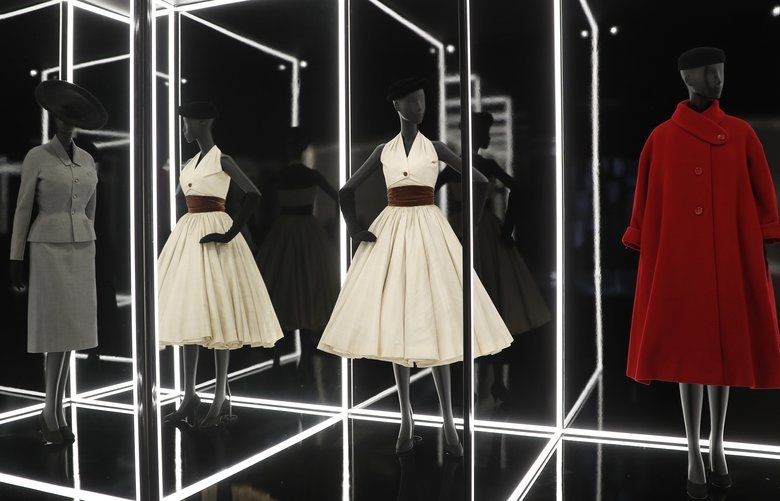 A selection of designs by Christian Dior for the Haute couture Autumn/Winter 1950/1952 season including a Romanesque Dress (1950) and red Ulysse Coat (1952), on display during a press preview of the largest exhibition in the United Kingdom of the Paris based fashion House of Dior at the V&A Museum in London, Wednesday, Jan. 30, 2019. Billed as the largest and most comprehensive exhibition ever staged in Britain on the revered fashion house, the exhibition traces the impact of Dior over seven decades and showcases dozens of spectacular couture gowns. (AP Photo/Alastair Grant) XAG110 XAG110 XAG110