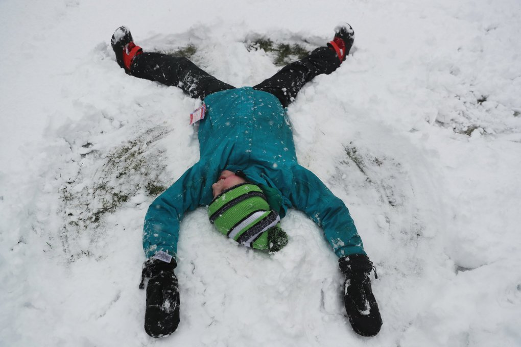 Maisey Jarrett, 11 , makes a snow angel with her sister in West Seattle on Friday. (Erika Schultz / The Seattle Times)