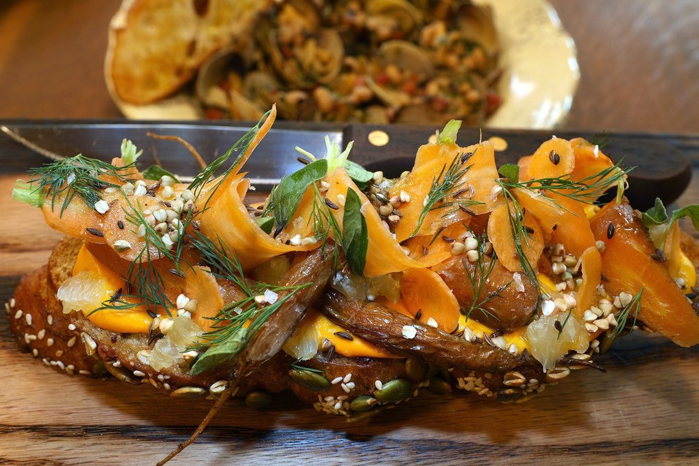The Hart and the Hunter, in downtown Seattle, offers a very colorful carrot tartine. In the background is a plate of little neck clams with black-eyed peas. (Greg Gilbert / The Seattle Times)