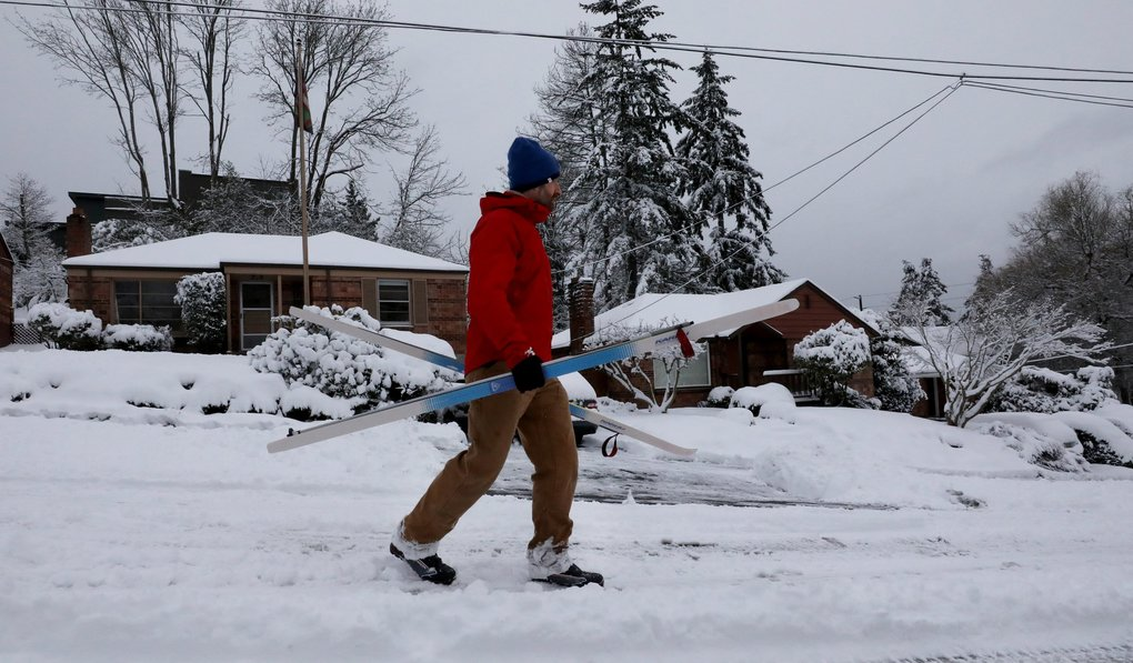 Cross-country skis in hand, David Hayward heads west on Northwest 56th Street.  He and his wife, Annie, had skied up the street. (Alan Berner / The Seattle Times)