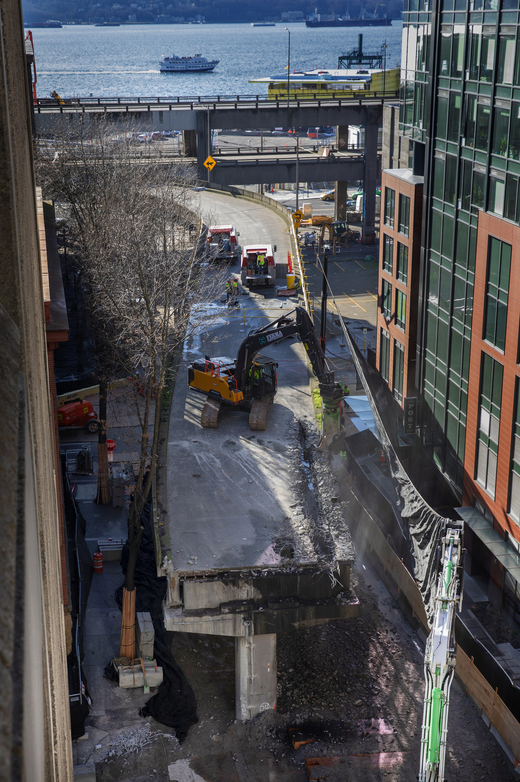 After a huge tarp was put in place to protect the adjacent building at right, demolition of the Columbia Street onramp to the Alaskan Way Viaduct proceeded Thursday. (Ellen M. Banner / The Seattle Times)