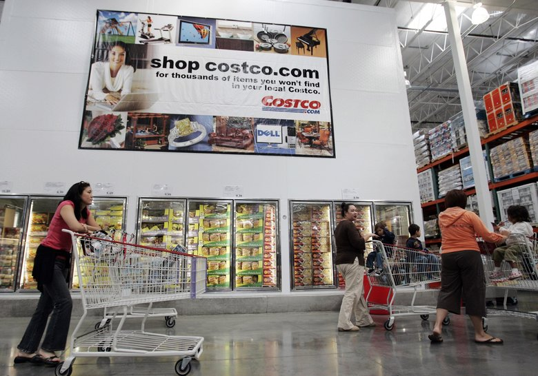 Costco shoppers walk next to an advertisement for Costco online at a Costco store in San Jose, Calif. The warehouse shopping club topped the Internet retail category in this year's annual American Customer Satisfaction Index. (Paul Sakuma / The Associated Press, 2017)
