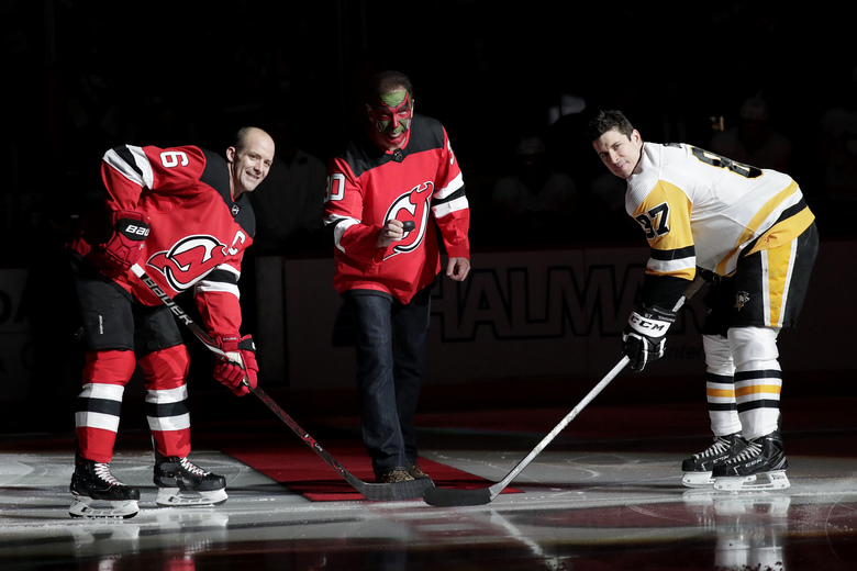 Actor Patrick Warburton, center, is dressed as Seinfeld cast member David Puddy, during a ceremonial puck drop with New Jersey Devils defenseman Andy Greene, left, and Pittsburgh Penguins center Sidney Crosby prior to an NHL hockey game, Tuesday, Feb. 19, 2019, in Newark, N.J. (AP Photo/Julio Cortez)
