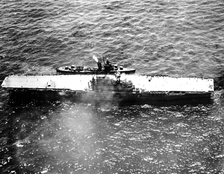 FILE – In this Oct. 26, 1942 file photo, the stricken aircraft carrier USS Hornet lies dead in the waters after a morning attack by Japanese warplanes during the Battle of Santa Cruz in the South Pacificduring World War II. A research vessel funded by the late Seattle billionaire Paul Allen has discovered the wreckage of the aircraft carrier sunk in the South Pacific. Allen's Vulcan Inc. announced this week of Feb. 10, 2019,  that an autonomous submarine sent by the crew of the research vessel Petrel found the USS Hornet nearly 17,500 feet (5,400 meters) deep near the Solomon Islands. The Hornet was best known for its part in the Doolittle Raid in April 1942, the first air attack on Japan. (AP Photo)