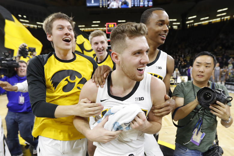 Iowa guard Jordan Bohannon, center, celebrates with teammates after an NCAA college basketball game against Northwestern, Sunday, Feb. 10, 2019, in Iowa City, Iowa. Bohannon made a three-point basket at the end of the game as Iowa won 80-79. (AP Photo/Charlie Neibergall)