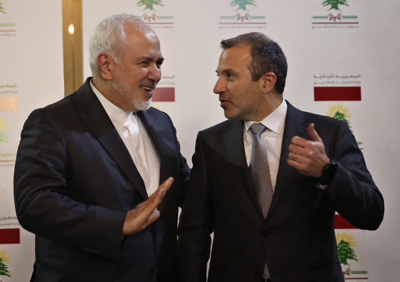 Lebanese Foreign Minister Gebran Bassil, right, speaks with his Iranian counterpart Mohammad Javad Zarif, in Beirut, Lebanon, Monday, Feb. 11, 2019. Zarif extended an offer for Iranian military assistance to the U.S.-backed Lebanese army on Sunday, saying Iran is ready to assist in all sectors should the Lebanese government want it. (AP Photo/Hussein Malla)