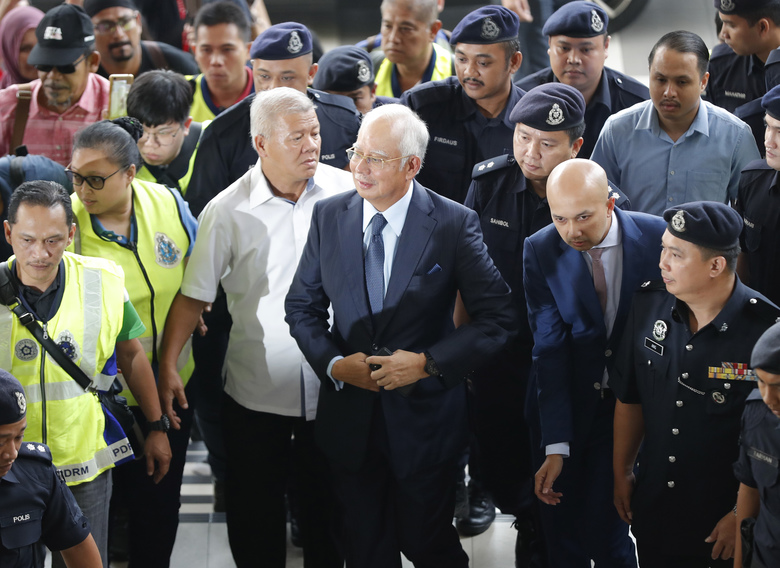 FILE – In this Oct. 4, 2018, file photo, former Malaysian Prime Minister Najib Razak, center, arrives at Kuala Lumpur High Court in Kuala Lumpur, Malaysia. Najib is hardly lying low ahead of his corruption trial set to begin Tuesday, Feb. 12, 2019, on charges related to the multibillion-dollar looting of the 1MDB state investment fund. He's crooned about slander in an R&B video and vilified the current government on social media to counter portrayals of him as corrupt and out of touch. Najib denies wrongdoing and his lawyers are seeking delay.(AP Photo/Vincent Thian, File)