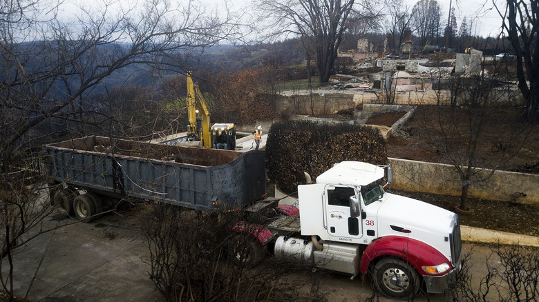 In this Feb. 8, 2019, photo, an excavator loads debris onto a truck while clearing a property burned by the Camp Fire in Paradise, Calif. In the 100 days since a wildfire nearly burned the town of Paradise off the map, the long recovery is just starting. Work crews have been cutting down trees and clearing burned-out lots, but Paradise is mostly a ghost town where survivors still dig for keepsakes in the foundations of their homes. (AP Photo/Noah Berger)