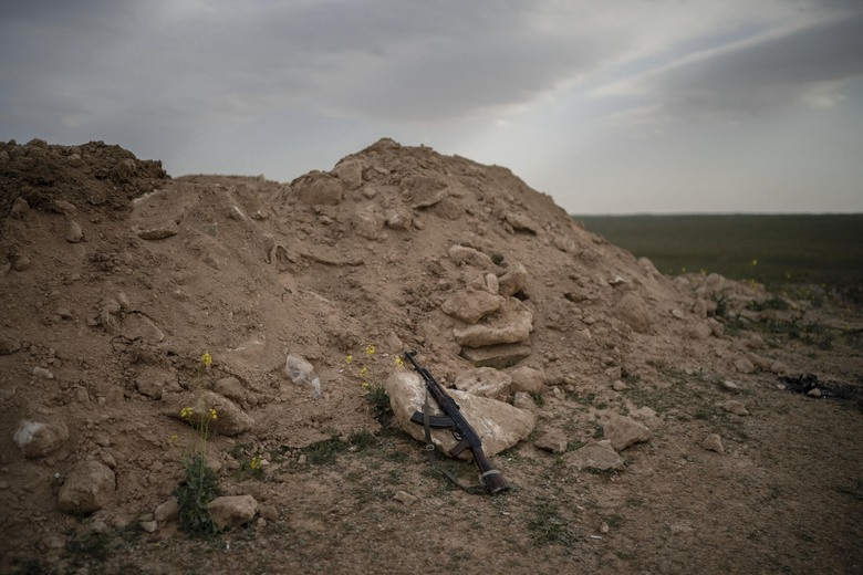 An AK-47 rifle, belonging to a U.S.-backed Syrian Democratic Forces (SDF) fighter, rests on a rock on a hill in the desert outside the village of Baghouz, Syria, Thursday, Feb. 14, 2019. U.S.-backed Syrian forces are clearing two villages in eastern Syria of remaining Islamic State militants who are hiding among the local population, and detaining others attempting to flee with the civilians, the U.S.-led coalition said Thursday. (AP Photo/Felipe Dana)