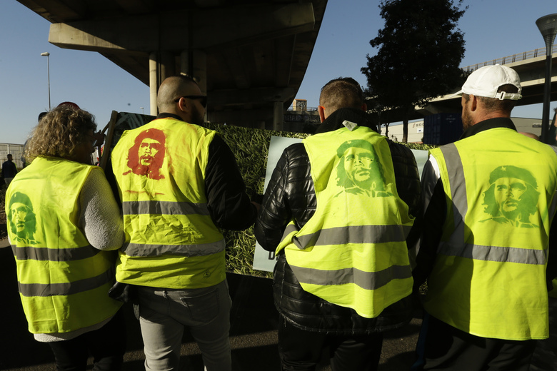Yellow vest protesters with portraits of Che Guevara on their vest march during a demonstration Saturday, Feb.16, 2019 in Marseille, southern France. Yellow vest protesters are holding scattered demonstrations around Paris and the rest of France amid waning support for their movement. (AP Photo/Claude Paris)