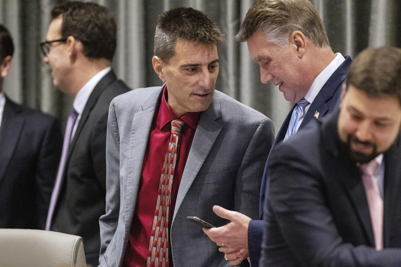 Dallas Woodhouse, executive director of the NC Republican Party, talks with Mark Harris, a Republican candidate in North Carolina's 9th Congressional race, during a break in the third day of a public evidentiary hearing on the 9th Congressional District voting irregularities investigation Wednesday, Feb. 20, 2019, at the North Carolina State Bar in Raleigh, N.C. (Travis Long/The News & Observer via AP)