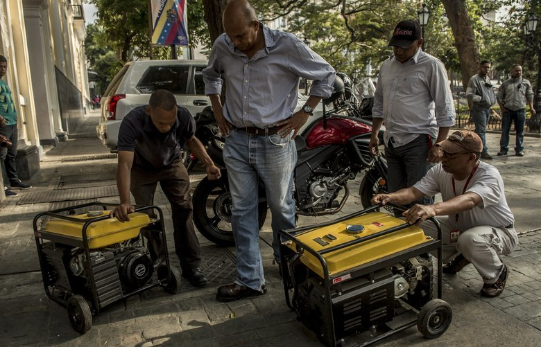 """Government workers struggling to get generators to work for want of oil, in downtown Caracas, Venezuela, on Friday, March 8, 2019. A widespread blackout had left much of Venezuela in darkness the night before. The government of President Nicolás Maduro blamed the blackout on right-wing """"criminals"""" sabotaging a major hydroelectric dam. (Meridith Kohut/The New York Times) XNYT71 XNYT71"""