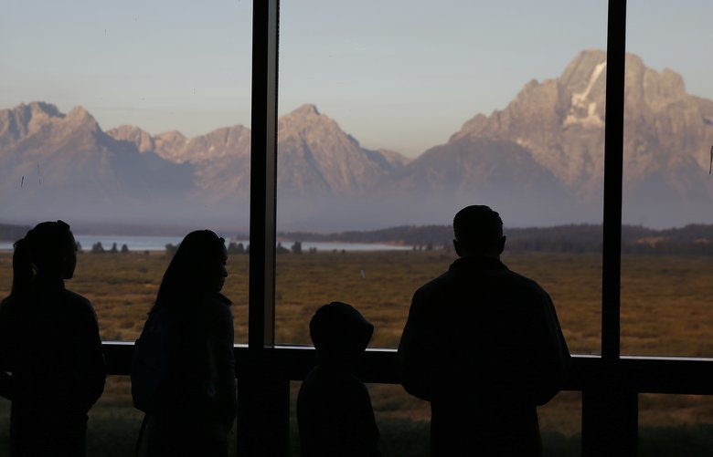 FILE – In this Aug. 28, 2016 file photo visitors watch the morning sun illuminate the Grand Tetons from within the Great Room at the Jackson Lake Lodge, in Grand Teton National Park, north of Jackson Hole, Wyo. Grand Teton National Park in western Wyoming seeks thoughts from the public on plans for a new network of cell towers amid questions about how the National Park Service balances public safety with the experience of wilderness. The park currently has two cell towers as part of a system built piecemeal-fashion, with some fiber-optic lines buried without conduit and poorly mapped. (AP Photo/Brennan Linsley,File) FX307 FX307