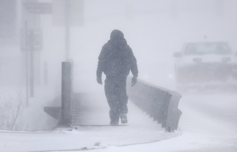 A man crosses Crow Creek during a blizzard on Wednesday, March 13, 2019, in Cheyenne, Wyo.  Heavy snow hit Cheyenne about mid-morning Wednesday and was spreading into Colorado and Nebraska.  (Jacob Byk/The Wyoming Tribune Eagle via AP) WYCHE103 WYCHE103