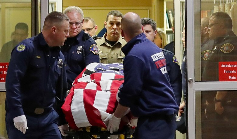 The body of Kittitas County Sheriff's deputy Ryan Thompson is draped with a U.S. flag as it is carried out of Kittitas Valley Healthcare Hospital early Wednesday in Ellensburg. (AP Photo / Ted S. Warren)