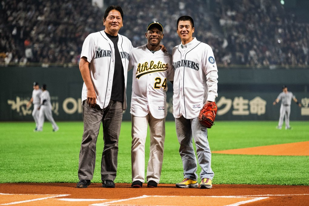 It's traditional for the ceremonial first pitch in Japan to have a full battery. Former Mariner Kaz Sasaki threw to former A's star Rickey Henderson. Receiving the pitch was former Mariners catcher Kenji Johjima. (Dean Rutz / The Seattle Times)