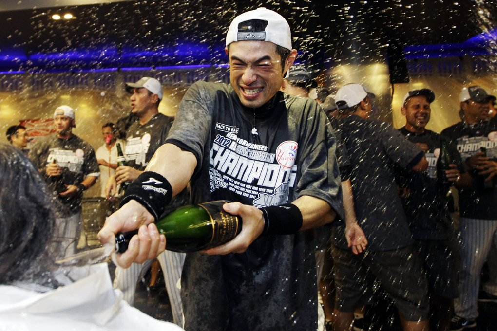 New York Yankees' Ichiro Suzuki douses the team photographer as teammates celebrate in the clubhouse after their 14-2 win over the Boston Red Sox in a baseball game and clinched the American League East title at Yankee Stadium in New York, Wednesday, Oct. 3, 2012.  (Kathy Willens / The Associated Press)