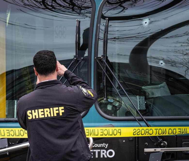 Bullet holes mar the windshield of a Metro bus on 125th Street Northeast in Seattle. (Dean Rutz / The Seattle Times)