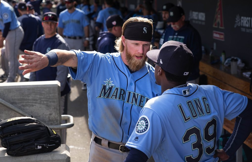 Jake Fraley and Shed Long talk hitting in the Mariner dugout Feb. 24 in Scottsdale, Ariz. (Dean Rutz / The Seattle Times)