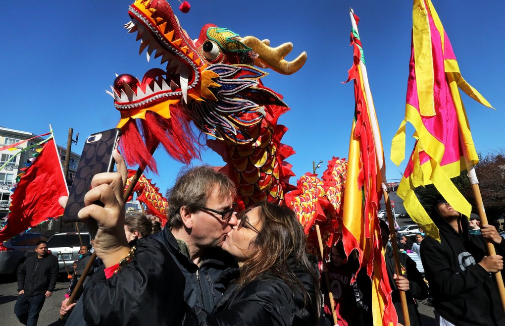 Gabriela Chávez photographs herself and her husband, Mitchel Mayberry, as a dragon swirls behind them during the Chinese Lunar New Year celebration in Seattle's Chinatown International District on Saturday. The event was rescheduled because of last month's winter storms. Chávez and Mayberry are newlyweds of four months.  (Alan Berner / The Seattle Times)