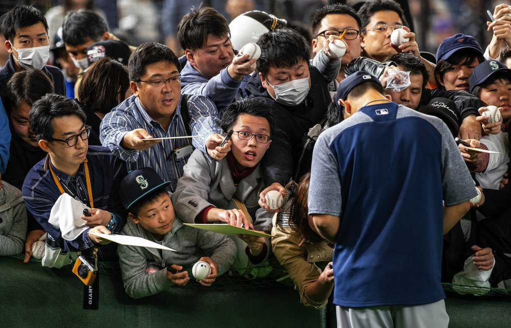 Fans along the left field wall clamour for an autograph from Yusei Kikuchi as the Mariners leave the field following batting practice Sunday.  The Seattle Mariners played the Yomiuri Giants of Japan in an exhibition game Sunday, March 17, 2019 at the Tokyo Dome in Japan. (Dean Rutz / The Seattle Times)