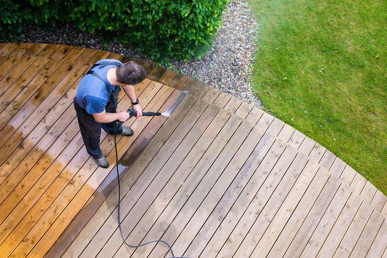 Power washing the deck blasts away grime and mildew, but it can be dangerous work, so it's best left to the pros. (Getty Images)