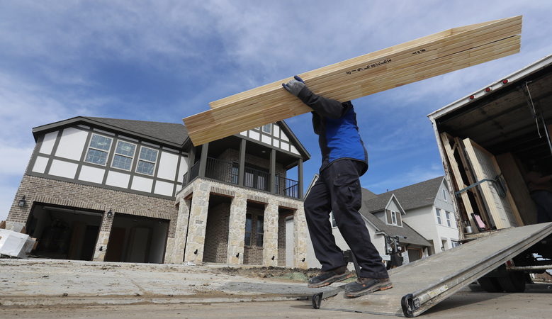 In this Feb. 20, 2019, photo a worker carries interior doors to install in a just completed new home in north Dallas. On Wednesday, March 13, the Commerce Department reports on U.S. construction spending in January.  (AP Photo/LM Otero)