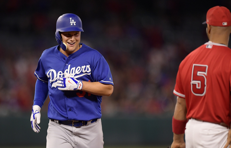 Los Angeles Dodgers' Joc Pederson, left, smiles at Los Angeles Angels first baseman Albert Pujols after being thrown out at second while trying to stretch a single into a double during the fifth inning of a preseason baseball game Monday, March 25, 2019, in Anaheim, Calif. (AP Photo/Mark J. Terrill)