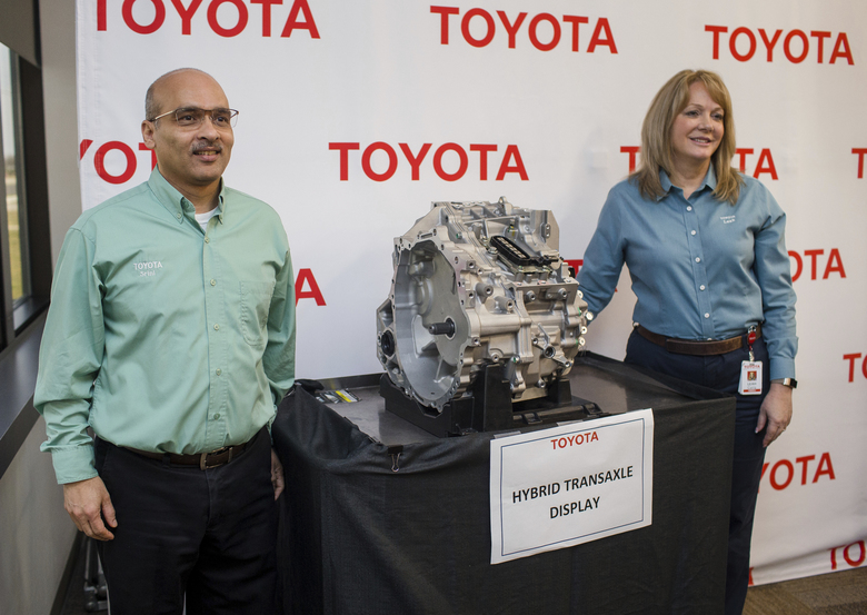 Toyota Motor Manufacturing West Virginia President Leah Curry, right, and Srini Matam, general manager for drivetrain, pose for a photo with a hybrid transaxle at Toyota Motor Manufacturing, Thursday, March 14, 2019, in Buffalo, W.Va. Toyota Motor Corp. on Thursday announced it is investing an additional $750 million at five U.S. plants. (Sholten Singer/The Herald-Dispatch via AP)