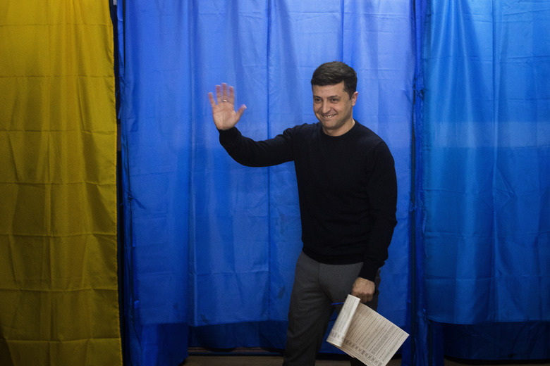 Ukrainian comedian and presidential candidate Volodymyr Zelenskiy waves to the media before casting his ballot at a polling station, during the presidential elections in Kiev, Ukraine, Sunday, March. 31, 2019. (AP Photo/Emilio Morenatti)