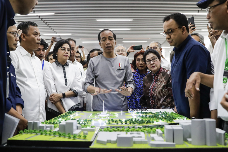 """Indonesian President Joko """"Jokowi"""" Widodo, center, inspects a model of Jakarta Mass Rapid Transit network during the inauguration ceremony of the subway line in Jakarta, Indonesia, Sunday, March 24, 2019. The 16-kilometer (10-mile) line system running south from Jakarta's downtown is the first phase of a development that if fully realized will plant a cross-shaped network of stations on the teeming city of 30 million people. (Mast Irham/Pool Photo via AP)"""