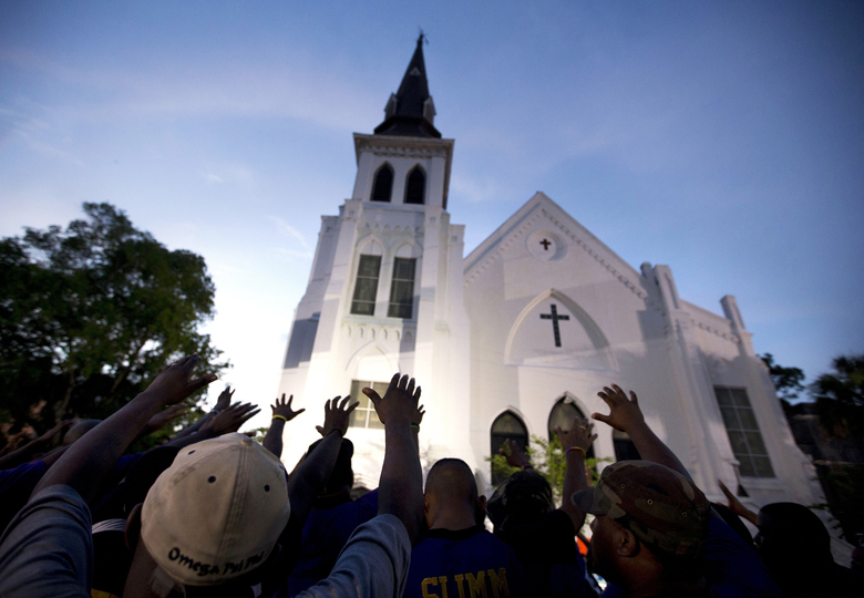 """FILE – In this June 19, 2015, file photo, the men of Omega Psi Phi Fraternity Inc. lead a crowd of people in prayer outside the Emanuel AME Church, after a memorial service for the nine people killed by Dylann Roof in Charleston, S.C. New Zealand's prime minister was hailed for her decisive response to the two mosque shootings by a white nationalist who killed 50 worshippers. For many Muslims, her most consequential move was immediately labeling the attack an act of terrorism. Community leaders and researchers say that for too long, terrorism was considered a """"Muslim problem"""" and that a double standard persists when attacker is white and non-Muslim. (AP Photo/Stephen B. Morton, File)"""