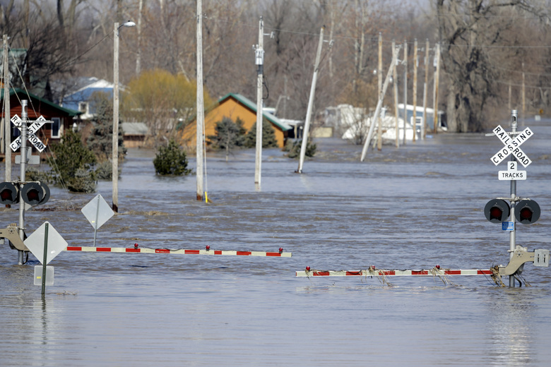 A railroad crossing is flooded with water from the Platte River, in Plattsmouth, Neb., Sunday, March 17, 2019. Hundreds of people remained out of their homes in Nebraska, but rivers there were starting to recede. The National Weather Service said the Elkhorn River remained at major flood stage but was dropping. (AP Photo/Nati Harnik)