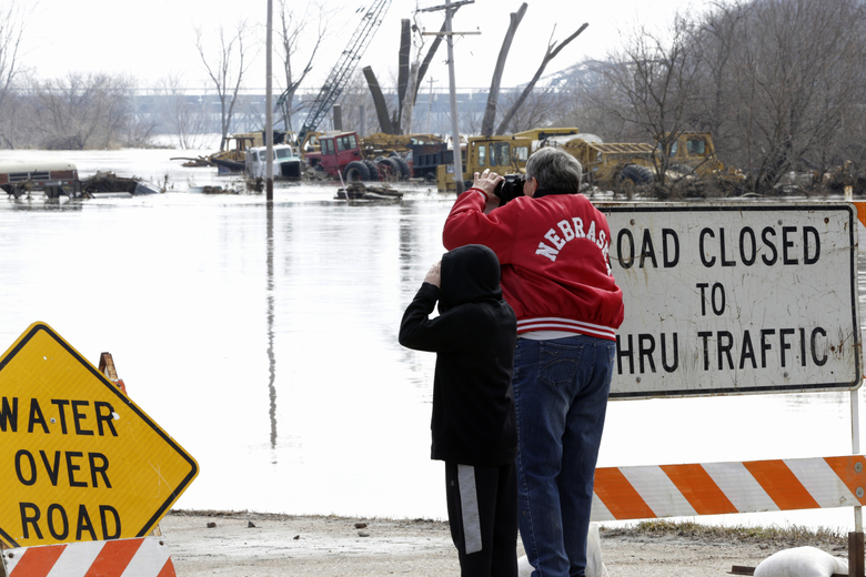 A woman wearing a Nebraska coat takes photos of flooded areas in Plattsmouth, Neb., Sunday, March 17, 2019. Hundreds of people remained out of their homes in Nebraska, but rivers there were starting to recede. The National Weather Service said the Elkhorn River remained at major flood stage but was dropping. (AP Photo/Nati Harnik)