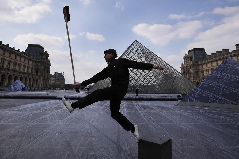 French street artist JR poses in the courtyard of the Louvre Museum near the glass pyramid designed by architect Leoh Ming Pei, in Paris, Wednesday, March 27, 2019 as the Louvre Museum celebrates the 30th anniversary of its glass pyramid. JR project is a giant collage of the pyramid to bring it out of the ground by revealing the foundations of the Napoleon courtyard where it is erected. (AP Photo/Francois Mori)