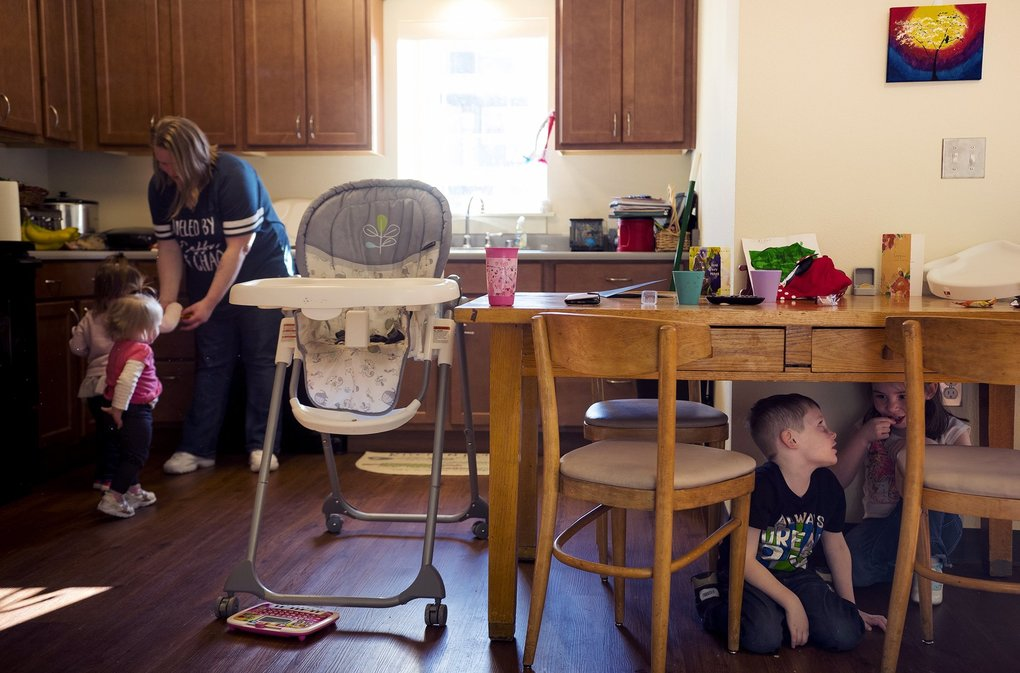 The kitchen in Cicelia Bracken's new apartment is a place for food  and play as two of her kids entertain themselves under the dining table. (Rajah Bose for The Seattle Times)